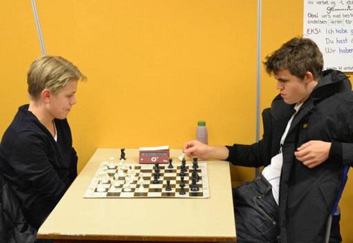 Magnus Carlsen fikk bryne seg på vår egen Lars Oskar Hauge (14). Foto: Olga Dolzhikova