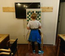 Axel Tunsjø WalkOver gjør sjakkoppgaver på endeveggen. (foto: WFM Sylvia Johnsen)